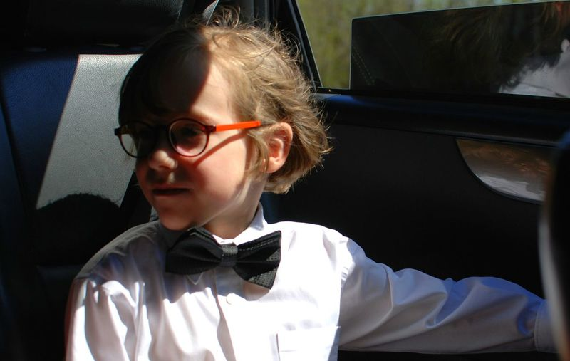 Boy wearing bow tie sitting in car during sunny day