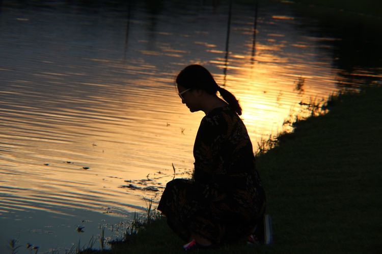 Silhouette woman kneeling by lake during sunset