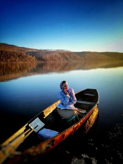 Man sitting on boat in lake against clear blue sky