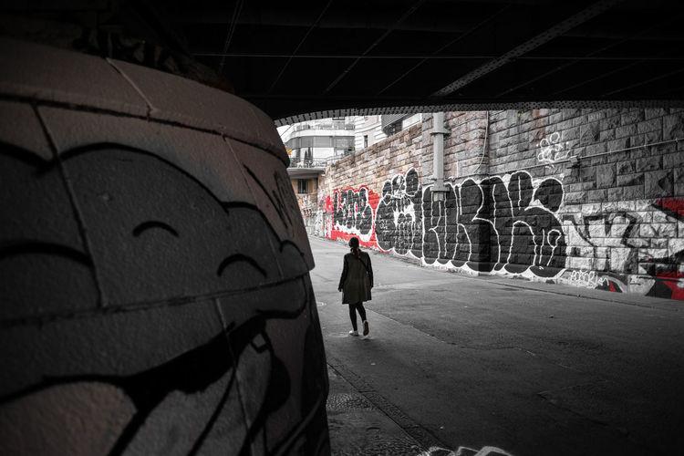 Rear view of man walking against graffiti wall