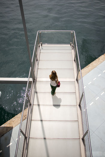 High angle view of woman on staircase by swimming pool