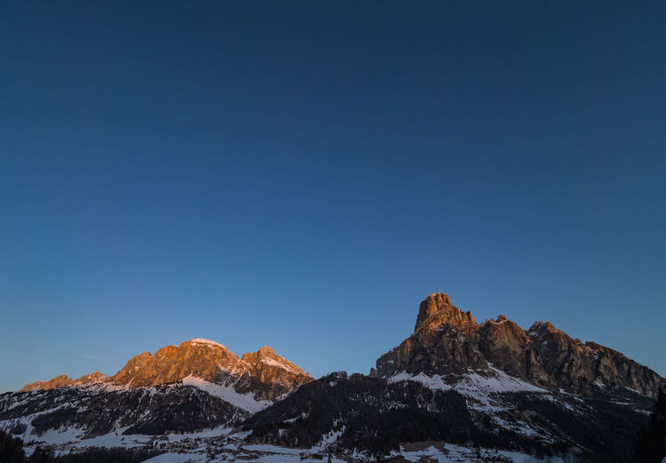Scenic view of snowcapped mountains against clear blue sky at sunrise
