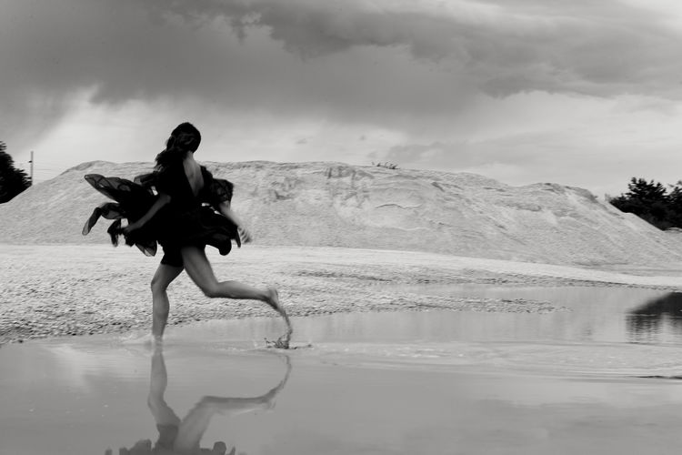 Cloudy Sky Run Running Beauty In Nature Black And White Blackandwhite Clothing Cloud - Sky Costume Floating Floating In Water Leisure Activity Lifestyles Mirroring In Water Monochrome Movement Nature Outdoors Real People Waterfront Young Women