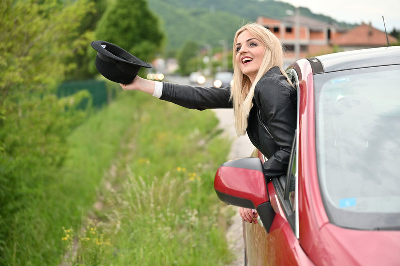 Woman smiling while sitting on car