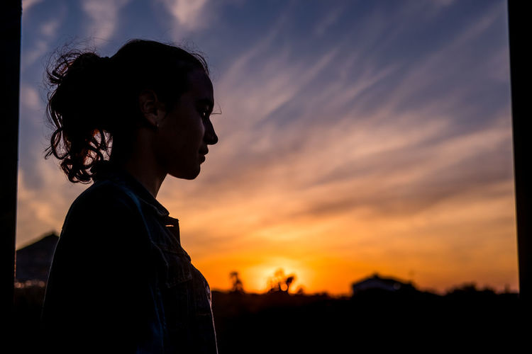 Side view of silhouette person against sky during sunset