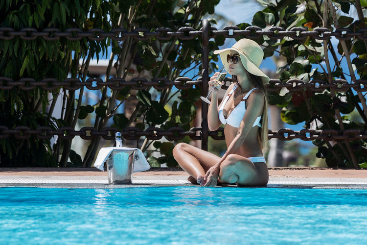 Woman In White Bikini Having Champagne While Sitting At Poolside