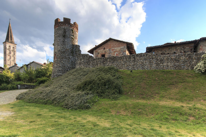 Candelo, Biella - May 4, 2016: Panoramic view of the Medieval village of Ricetto di Candelo in Piedmont, used as a refuge in times of attack during the Middle Age. Architecture Biella Building Exterior Built Structure Candelo Candelo In Fiore Castle Cloud Cloud - Sky Cloudy Day Exterior Grass Green Color History Italy Lawn Medieval Village No People Outdoors Plant Ricetto Di Candelo  Sky The Past Travel Destinations