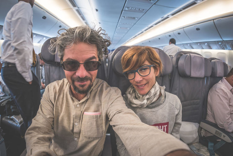 Cheerful adult caucasian couple taking selfie inside plane. Fish eye view from below. Concept of people traveling, natural light. Keywords: plane,couple,selfie,people,traveling,airplane,travel,fisheye,man,woman,mobile,journey,two,posing,positive,looking at camera,adult,flight,aircraft,face,caucasian,lifestyle,transportation,happy,fish eye,inside,looking,expression,facial,cabin,cheerful,family,smiling,beautiful,boarding,phone,smartphone,young,female,fun,portrait,fashion,senior,male,casual,flying,persons,vacation,sitting Adult Air Vehicle Airplane Airplane Seat Commercial Airplane Day Flying Indoors  Lifestyles Men People Real People Transportation Travel Vehicle Interior Vehicle Seat Warm Clothing Young Adult Young Women