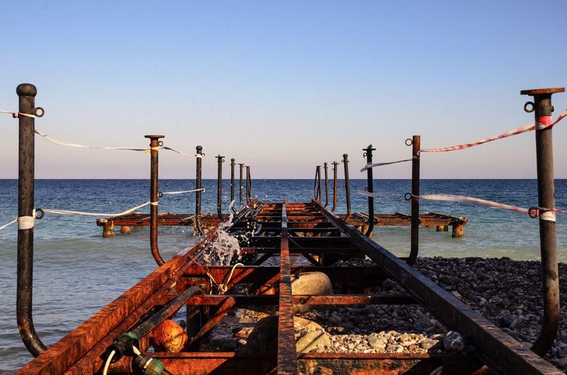 Wrought iron jetty leading to calm blue sea