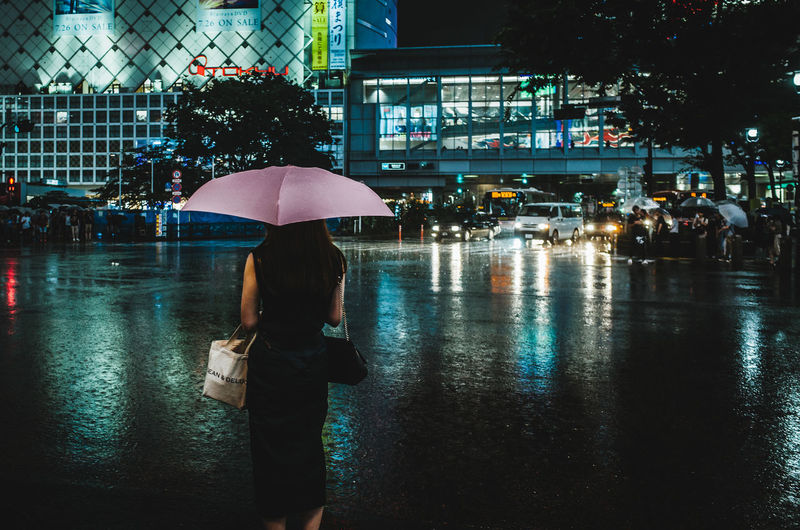 Rear view of woman with umbrella on street during monsoon at night