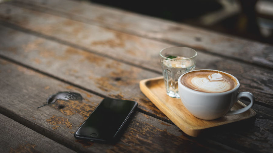 latte art and my Phone Latte Cappuccino Coffee Coffee - Drink Coffee Cup Communication Crockery Cup Drink Food And Drink Freshness Frothy Drink Glass Hot Drink Indoors  Latte Latteart Mug No People Portable Information Device Refreshment Smart Phone Tray Wireless Technology Wood - Material