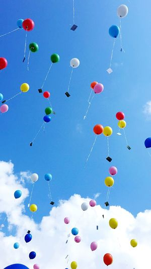 Low angle view of colorful balloons flying against sky