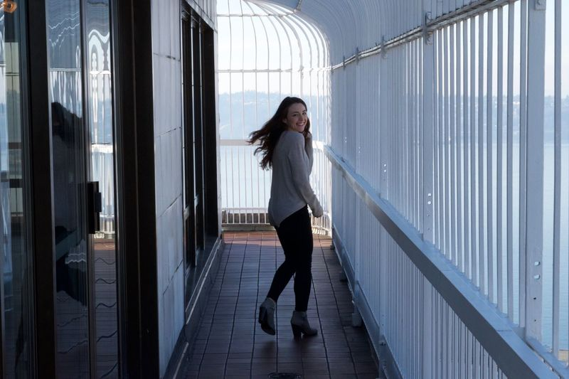 Portrait of happy young woman running in balcony at smith tower