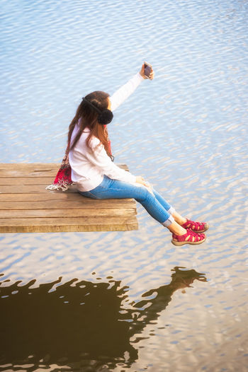 High angle view of woman taking selfie on mobile phone while sitting on pier over lake