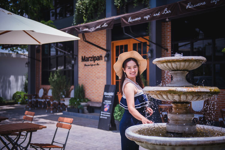 Portrait of smiling young woman at outdoor cafe