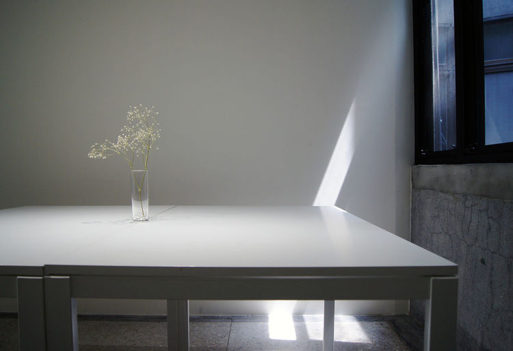 Vase on table against wall