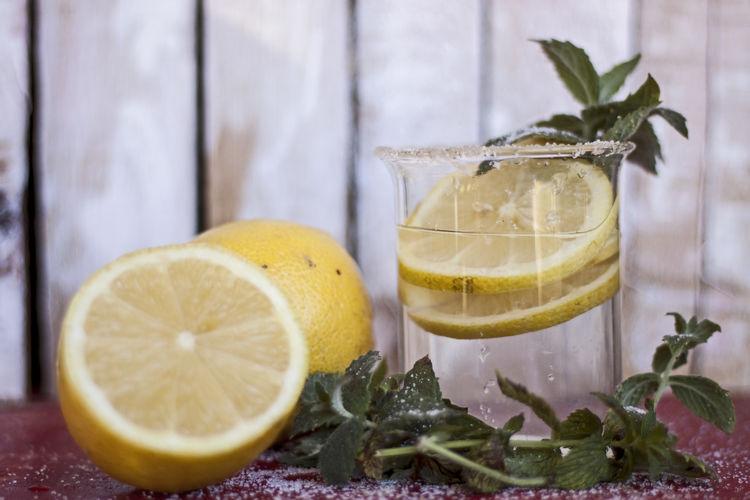 Close-up of lemonade by lemons on table