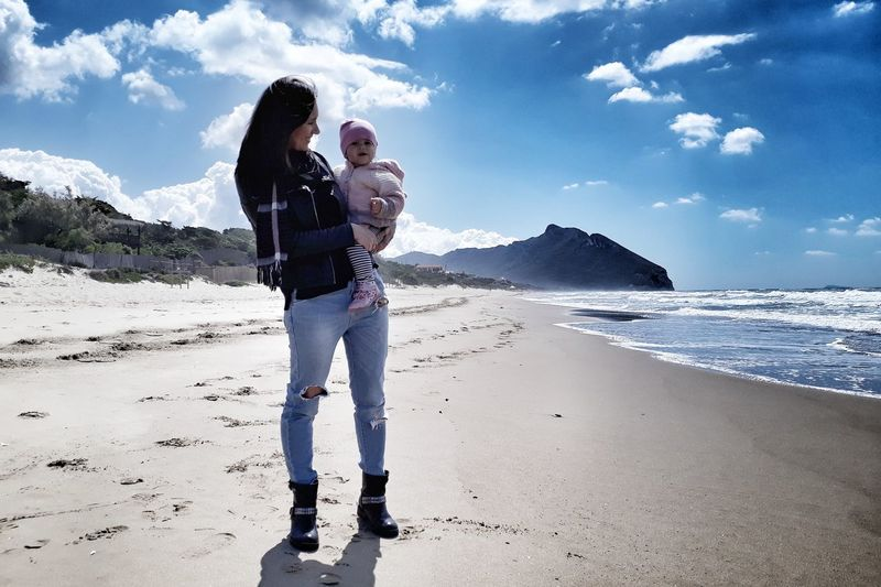 Mother carrying daughter at beach against blue sky