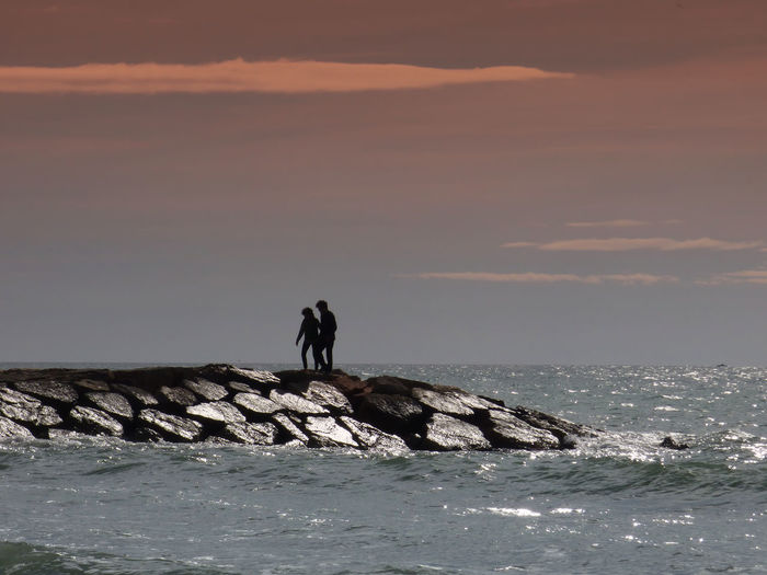 Beach Beauty In Nature Couple Contemplating The Sea From The Breakwater Day Nature Outdoors Scenics Sea Sky Sunset Water