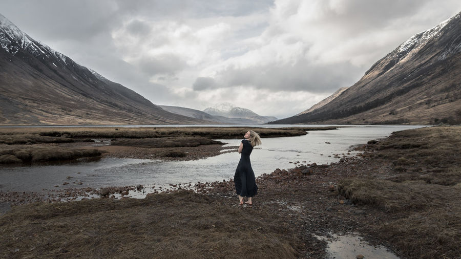 Fine Art Photograph of a woman in Glen Etive Canonphotography Canon EOS 750D 10-18mm Scotland Fine Art Photography The Great Outdoors - 2018 EyeEm Awards The Creative - 2018 EyeEm Awards Scenics Nature Female Art Blonde Girl Sensual_woman Wind Glen Etive Ralph Lauren Dress Water Mountain Lake Women Adventure Atmospheric Mood Dramatic Landscape
