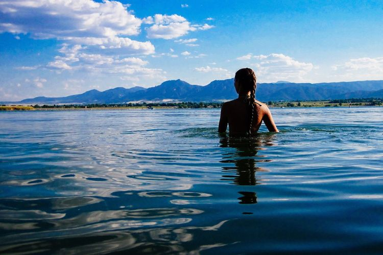 Rear view of woman with braided hair in lake against sky