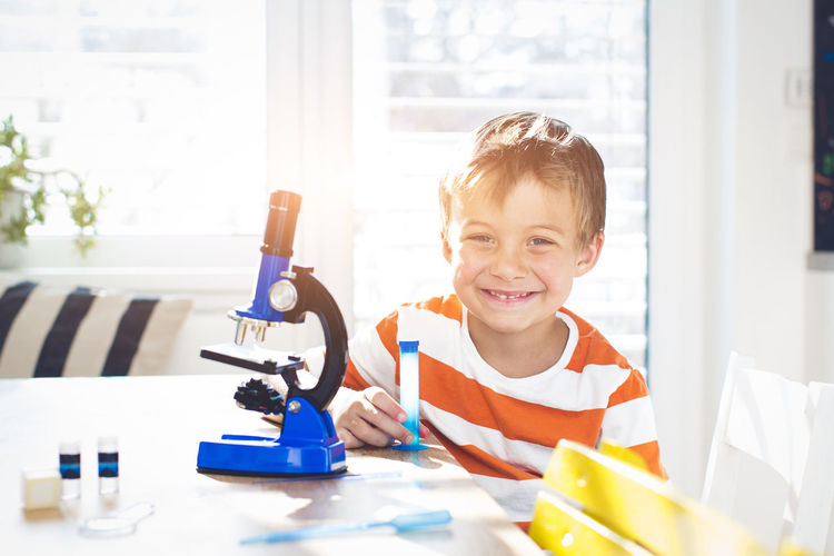 Portrait of smiling boy doing science experiment at home