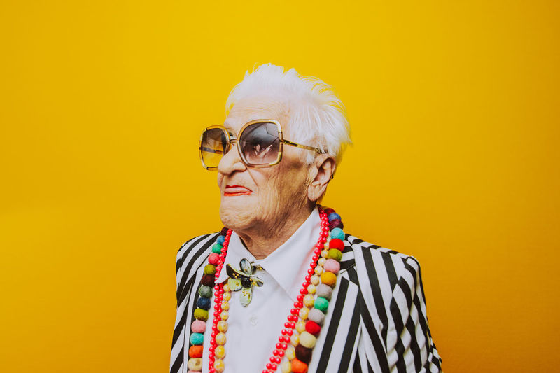 Close-up of thoughtful senior woman wearing sunglasses against yellow background