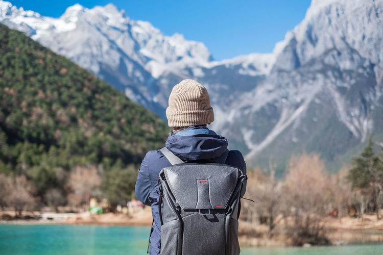 Rear view of man wearing backpack while standing against mountains during winter
