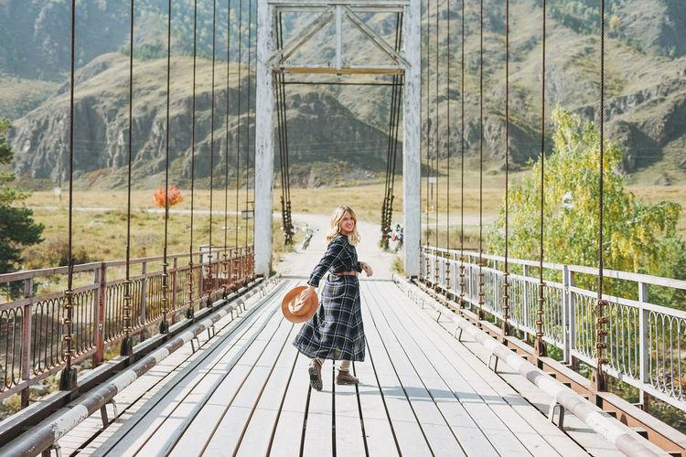 Portrait of woman walking on footbridge