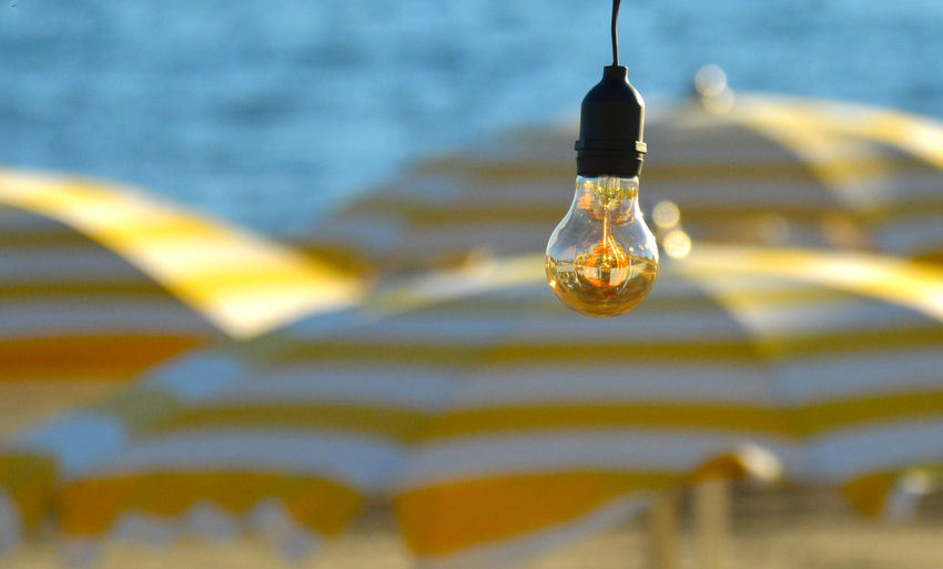 Close-up of light bulb hanging on water
