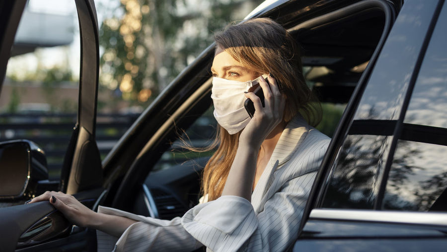Portrait of young woman using mobile phone in car