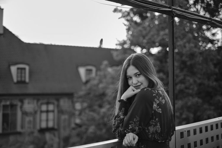 Portrait of young woman standing in balcony