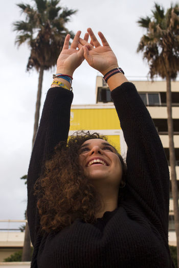 Smiling young woman with arms raised in city