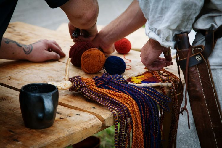Midsection Of Men Making Wool Craft Product On Table