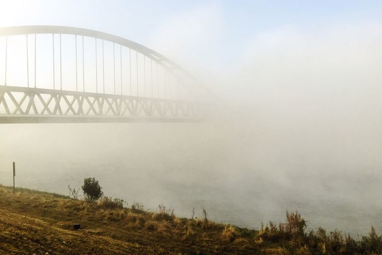 Bridge over river in foggy weather