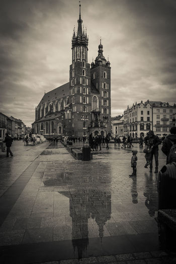 Black and white view of St. Mary Basilica in old city center in Krakow Krakow City Town Saint Mary Basilica Puddle Rainy Day Religion Urban Reflection Amazing View Architecture Skyline Buildings Travel Destinations Travel Traveling Travel Photography Streetphotography Street Building Exterior Built Structure Sky Place Of Worship Building Cloud - Sky Belief Group Of People Spirituality Large Group Of People Water Rain Outdoors