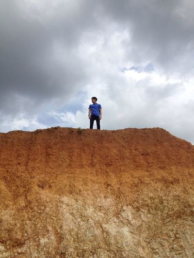 Man standing on agricultural field against storm clouds