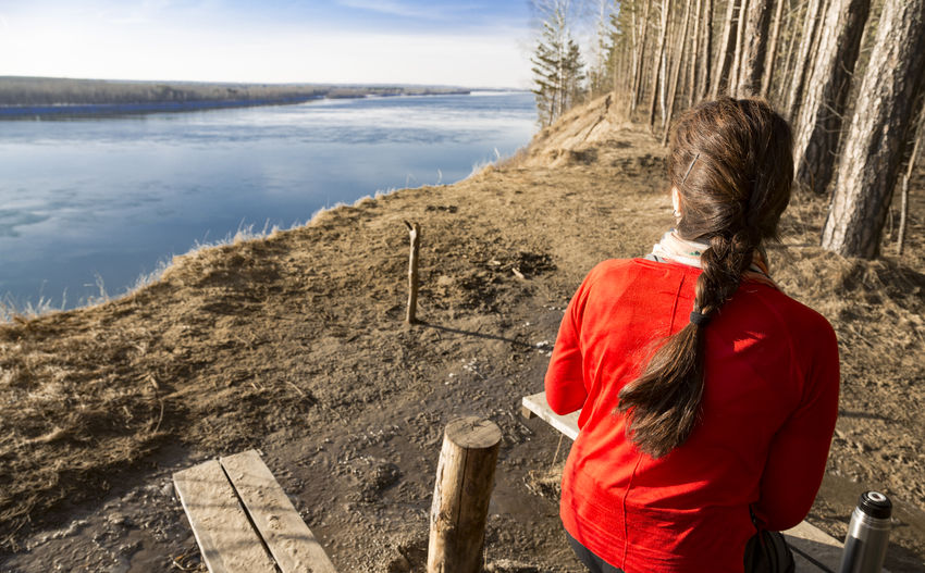 Rear view of woman looking at landscape while sitting on riverbank