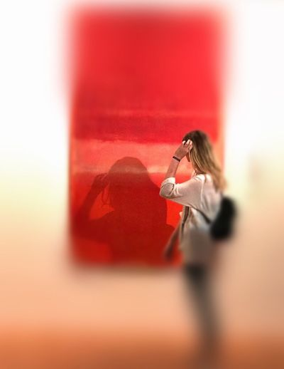 Side view of woman with red umbrella