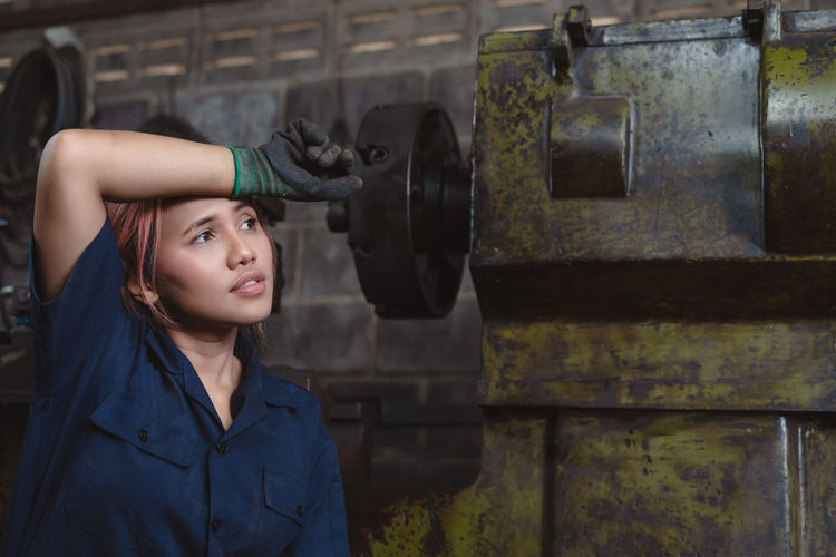 Female factory worker wiping sweat from her head with her arm looking away from camera