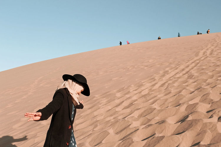 Man and woman on sand dune in desert against clear sky