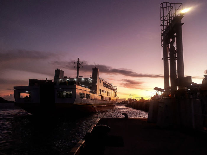 sunset in bakauhuni lampung, february 2019 First Eyeem Photo Sunrise Large Ship Ship Oil Industry Outdoors Illuminated Built Structure Nautical Vessel Building Exterior No People Water Fuel And Power Generation Architecture Business Mode Of Transportation Factory Cloud - Sky Transportation Nature Industry Sunset Sky