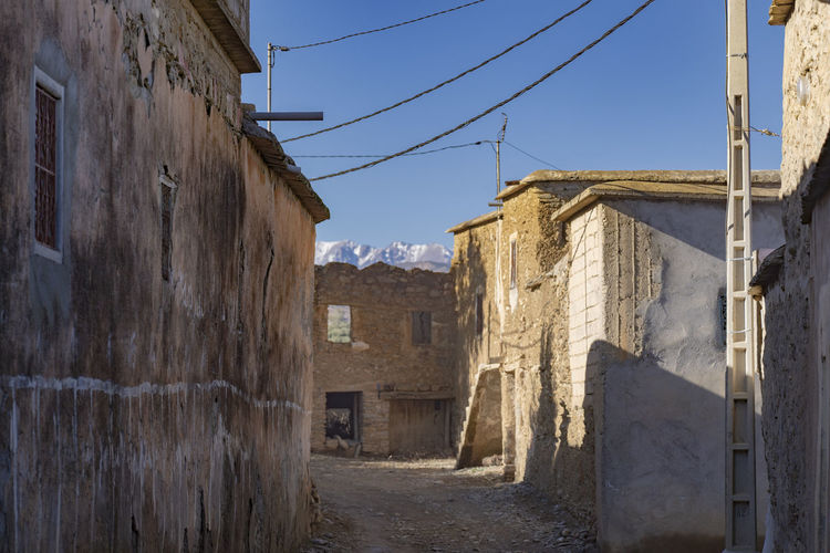 Village Stone Buildings Stone Wall Dirt Road Electricity  Blue Sky Mountains In Distance Mountains In Background High Alpine Alpine Village High Altitude Village Settlement Morocco Atlas Mountains Alleyway Narrow Narrow Street Cool Morning Morning Light No People Empty Streets Row Of Houses Row Of Buildings Ancient