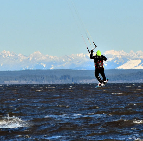 Rear view of a male kite surfer in action