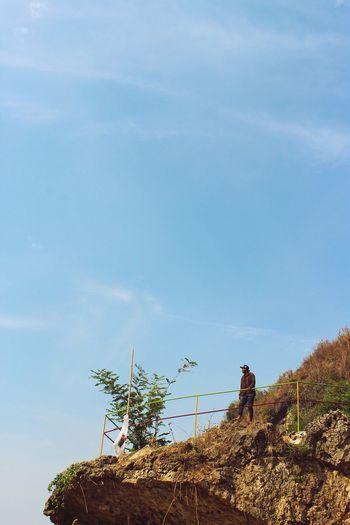 Man by tree against sky