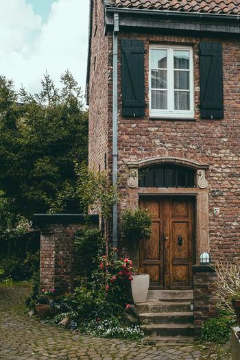 Streets of Dusseldorf Plant Architecture Built Structure Building Exterior Building Entrance Door Nature House Tree No People Window Growth Day Flower Flowering Plant Residential District Outdoors Potted Plant Wall Brick Flower Pot