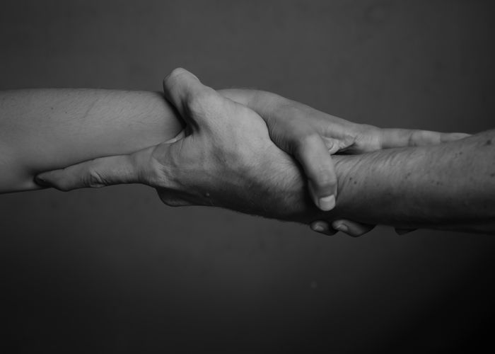 Close-up Of Holding Hands Against Gray Background