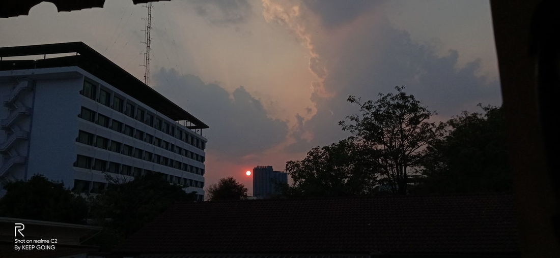 Low angle view of buildings against sky at sunset