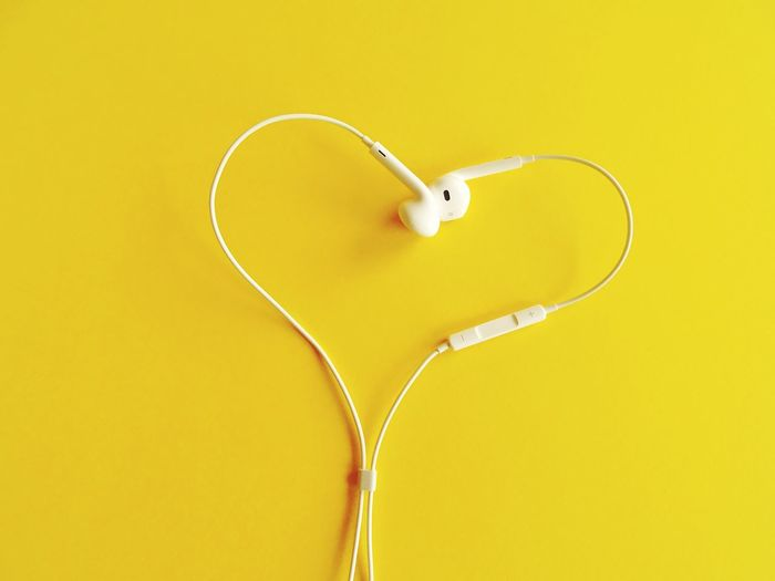 Earphones on yellow background Audio Equipment Audio EyeEm Selects Yellow Indoors  No People Copy Space Still Life Single Object Technology Connection Heart Shape Headphones Studio Shot Cable Close-up Colored Background Directly Above Listening Communication Simplicity Yellow Background Music