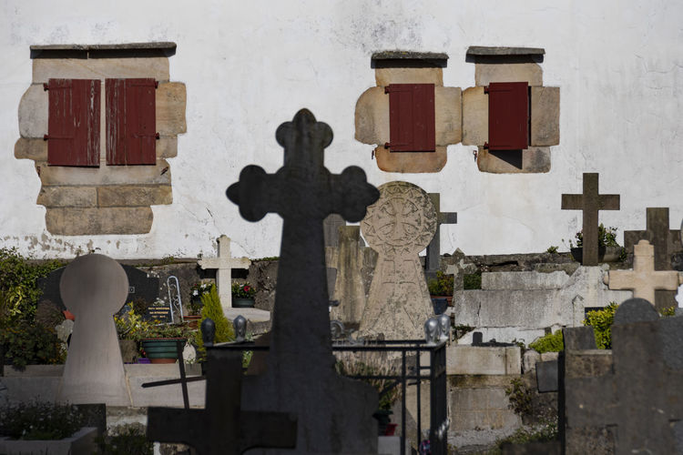 CROSSES Built Structure Tombstone Cemetery Architecture Grave Art And Craft Religion Human Representation Representation Cross Sculpture Spirituality Stone Building Building Exterior Belief Day Stone Material No People Window Exceptional Photographs France Travel Rural Scene Cemetery